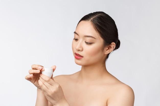 Mulher jovem e bonita na parede isolada branca, segurando o creme cosmético, asiático