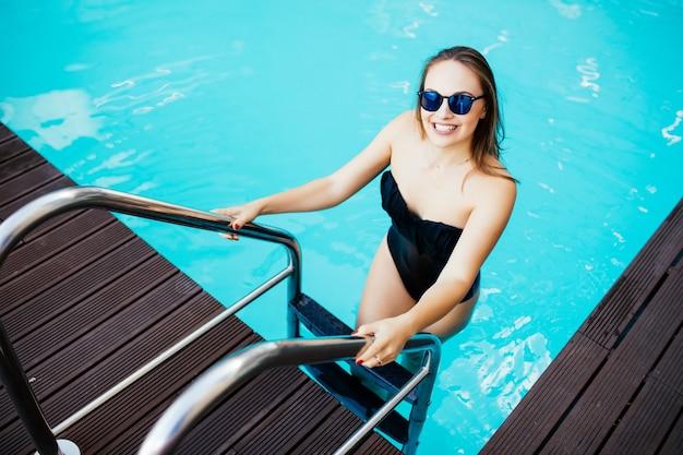 Mulher jovem e bonita na piscina segurando o corrimão