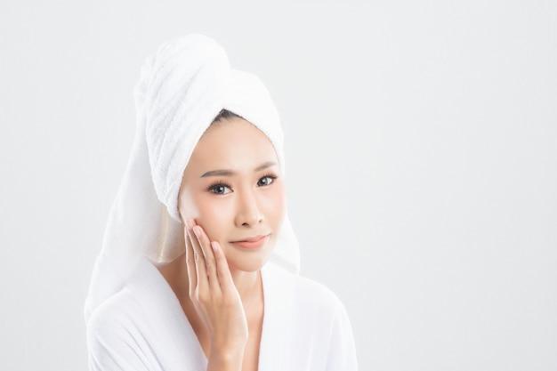 Mulher jovem e bonita na toalha de banho está tocando seu rosto e sorrindo, isolado no fundo branco. mulher após o banho com a pele limpa e perfeita.