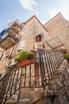 Mulher jovem e bonita na varanda de uma velha casa de pedra