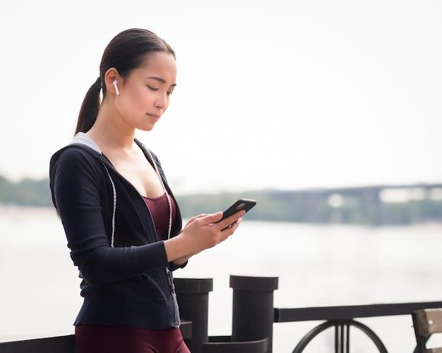 Mulher jovem e bonita navegação no telefone móvel