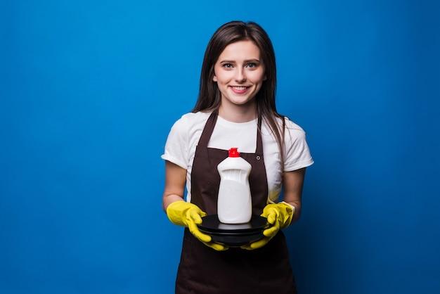 Mulher jovem e bonita no avental com pratos lavados e sabão. um frasco de detergente com um rótulo em branco em uma pilha de pratos limpos