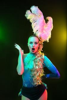 Mulher jovem e bonita no carnaval e fantasia de baile de máscaras com luzes de néon coloridas