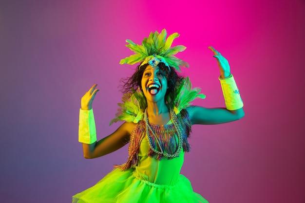 Mulher jovem e bonita no carnaval e fantasia de baile de máscaras em fundo gradiente de estúdio em luz de néon