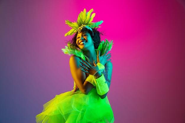 Mulher jovem e bonita no carnaval e fantasia de baile de máscaras em gradiente em luz de néon