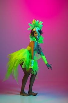 Mulher jovem e bonita no carnaval, elegante fantasia de baile de máscaras com penas dançando na parede gradiente em neon