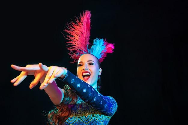 Mulher jovem e bonita no carnaval, elegante fantasia de baile de máscaras com penas na parede preta com luz de néon