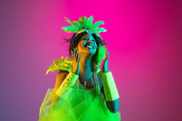 Mulher jovem e bonita no carnaval, fantasia elegante de baile de máscaras com penas dançando na parede gradiente com luz de néon