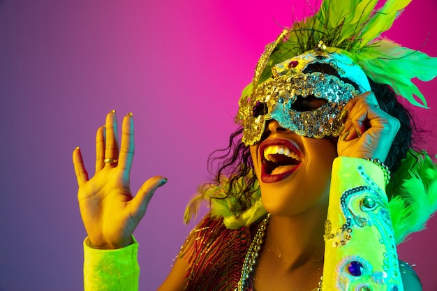 Mulher jovem e bonita no carnaval, fantasia elegante de baile de máscaras com penas na parede gradiente em luz de néon
