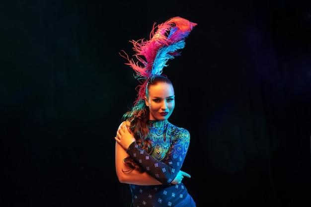 Mulher jovem e bonita no carnaval, fantasia elegante de baile de máscaras com penas na parede preta com luz neon