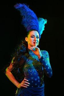 Mulher jovem e bonita no carnaval, traje de baile elegante com penas em fundo preto em luz de néon.