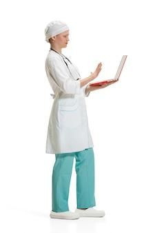 Mulher jovem e bonita no jaleco branco posando com laptop