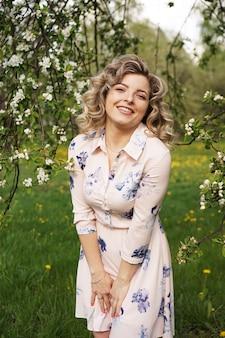 Mulher jovem e bonita no jardim de maçãs em um dia ensolarado de primavera - momentos felizes