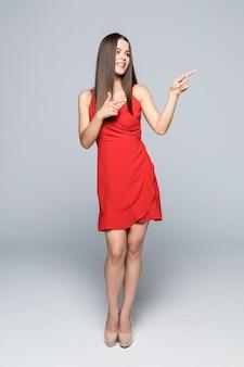 Mulher jovem e bonita no mini vestido vermelho e salto alto está de pé, apresentando algo e olhando para longe. vista lateral. tiro de comprimento total isolado no branco.