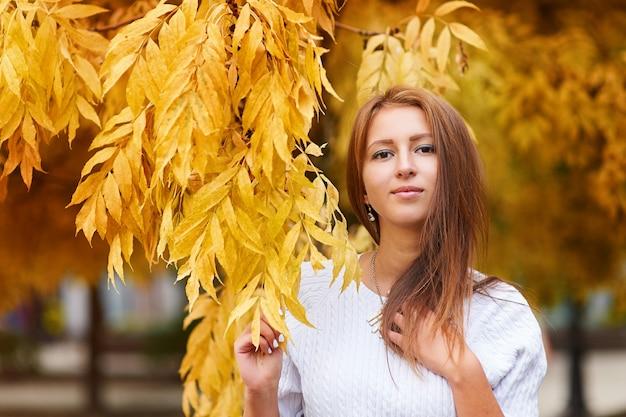 Mulher jovem e bonita no parque outono com folhas amarelas.