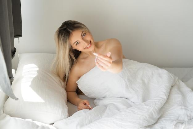 Mulher jovem e bonita no quarto com manta branca e gesto sedutor