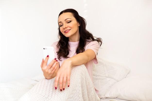 Mulher jovem e bonita no quarto sentada na cama com um telefone celular