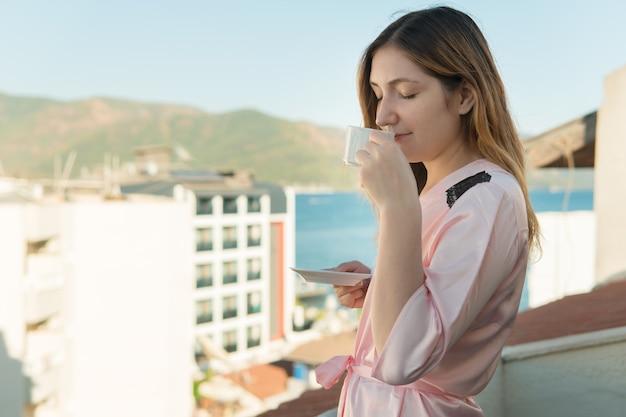 Mulher jovem e bonita no roupão de banho, bebendo chá em pé na varanda do seu quarto no hotel durante as férias, num contexto de bela natureza, o mar e as casas.