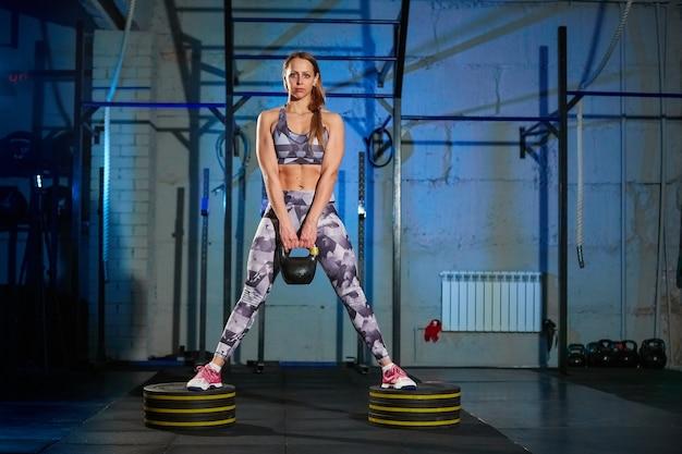 Mulher jovem e bonita no sportswear cinza fazendo exercício com peso