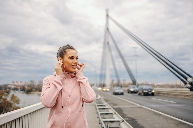 Mulher jovem e bonita no sportswear em pé na ponte, colocando fones de ouvido e se preparando para fazer jogging. fitness ao ar livre no conceito de tempo nublado.