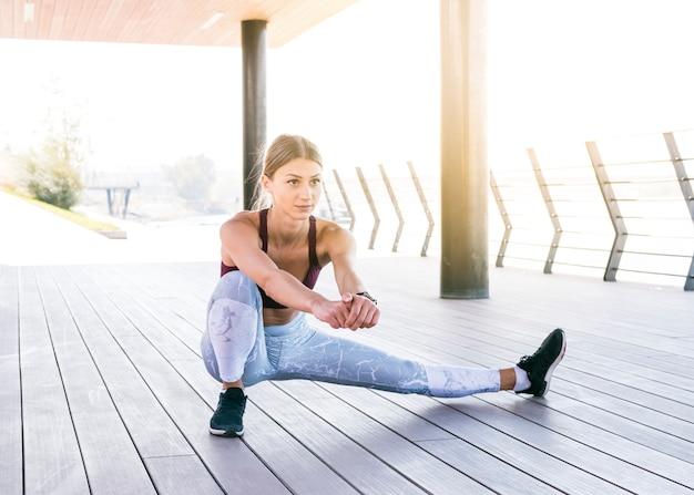 Mulher jovem e bonita no sportswear fazendo exercícios de alongamento