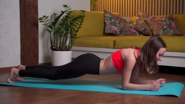 Mulher jovem e bonita no sportswear fazendo exercícios de prancha em um tapete de ioga à noite em casa.