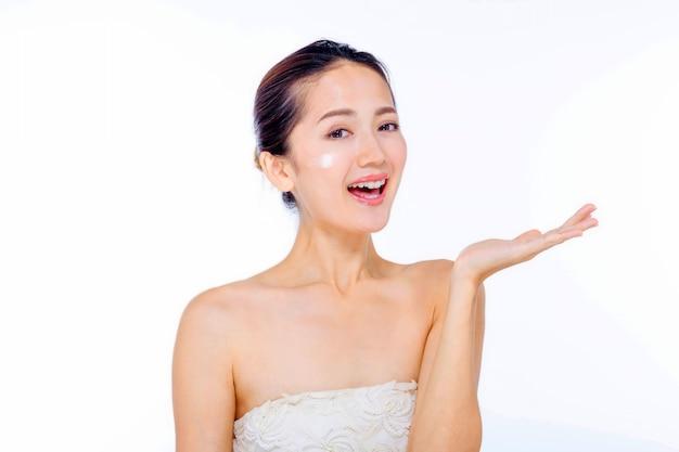 Mulher jovem e bonita no vestido branco com pele fresca limpa toque próprio rosto