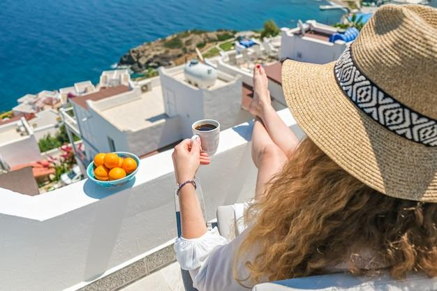 Mulher jovem e bonita no vestido branco e chapéu de palha e xícara de café sentada na varanda do terraço branco de casa ou hotel com vista para o mar.