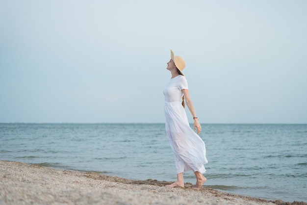 Mulher jovem e bonita no vestido branco e chapéu na praia. garota aristocrata na beira-mar