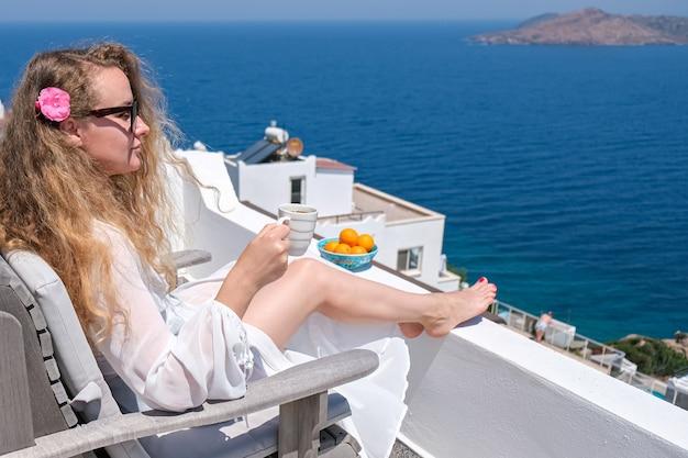 Mulher jovem e bonita no vestido branco flor no cabelo e xícara de café, sentada na varanda do terraço branco de casa ou hotel com vista para o mar.