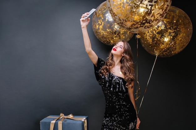 Mulher jovem e bonita no vestido de luxo preto, lábios vermelhos, cabelo castanho longo cacheado, tendo o retrato de selfie com grandes balões cheios de enfeites dourados. hora da festa, emoções verdadeiras.