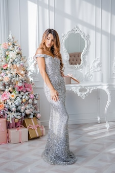 Mulher jovem e bonita no vestido de noite perto de árvore de natal. feliz natal