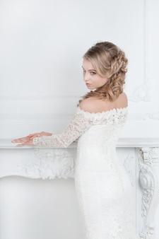 Mulher jovem e bonita no vestido de noiva em pé no salão nupcial.