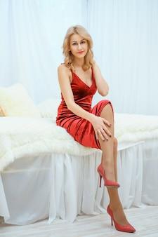 Mulher jovem e bonita no vestido vermelho deitada sentada na cama