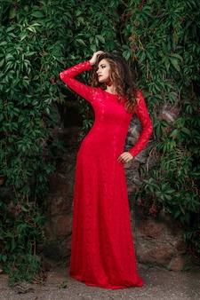 Mulher jovem e bonita no vestido vermelho longo