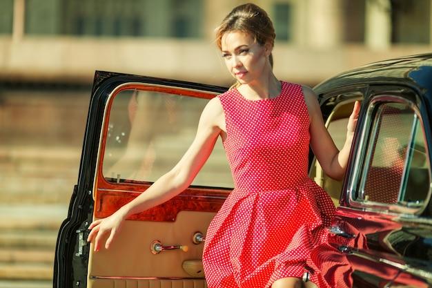 Mulher jovem e bonita no vestido vintage com auto retrô