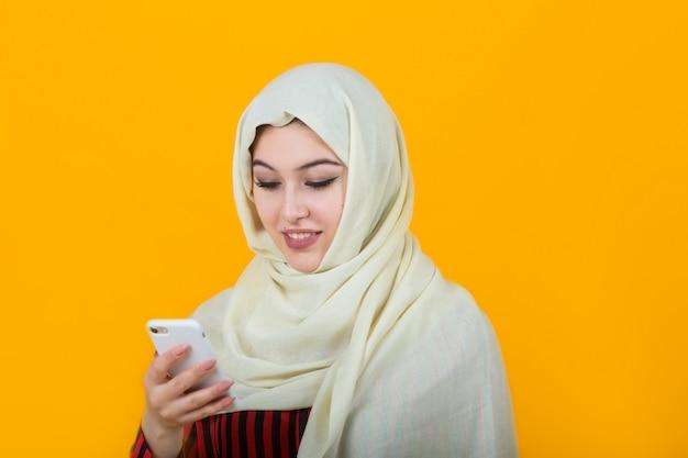 Mulher jovem e bonita no xaile muçulmano com telefone