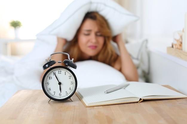 Mulher jovem e bonita odeia acordar de manhã cedo. menina com sono olhando para o despertador e tentando se esconder debaixo do travesseiro