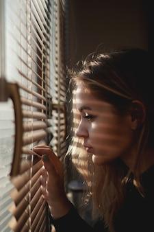 Mulher jovem e bonita olhando através das cortinas