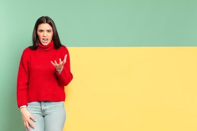 Mulher jovem e bonita olhando com raiva, irritada e frustrada gritando wtf ou o que há de errado com você. copie o espaço para colocar o seu conceito