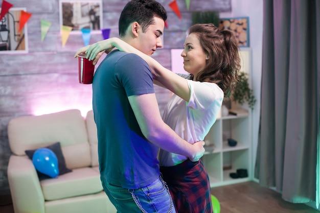 Mulher jovem e bonita olhando nos olhos do namorado enquanto dançava na festa de amigos.