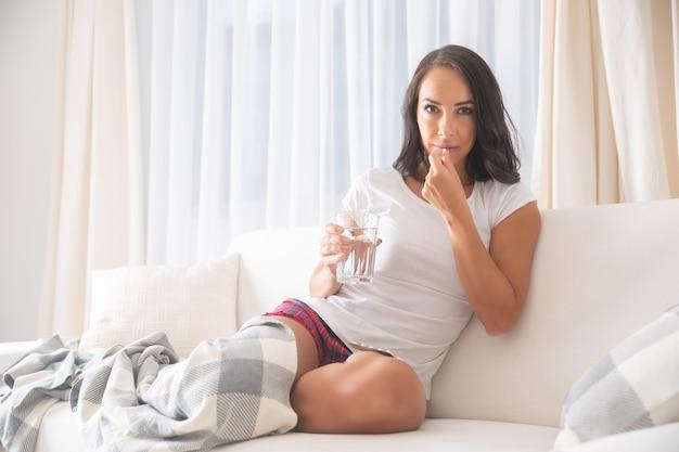 Mulher jovem e bonita olhando para a câmera, tomando um comprimido em um sofá segurando um copo d'água enquanto está sentado doente na sala de estar de cores claras.