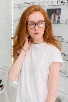Mulher jovem e bonita olhando para longe e posando na loja de óptica