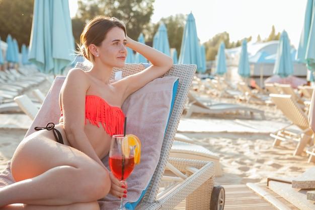 Mulher jovem e bonita olhando para longe, pensativa, sentado na praia, copie o espaço. atraente turista feminina descansando ao lado da piscina do hotel