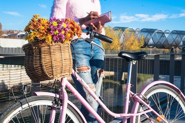 Mulher jovem e bonita olhando para sua agenda pelo rio com bicicleta vintage
