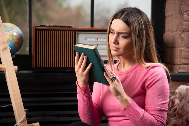 Mulher jovem e bonita olhando para um livro em casa