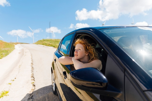 Mulher jovem e bonita olhando pela janela do carro