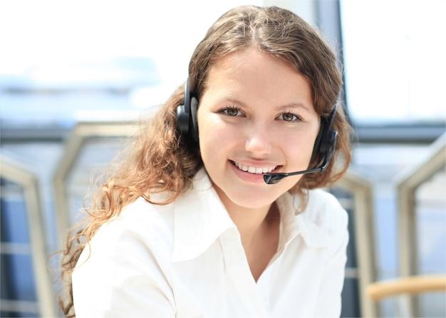 Mulher jovem e bonita operadora de call center com fone de ouvido no escritório