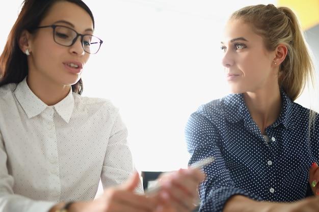 Mulher jovem e bonita ouve um colega triste entre os funcionários do escritório discutindo planos de projeto