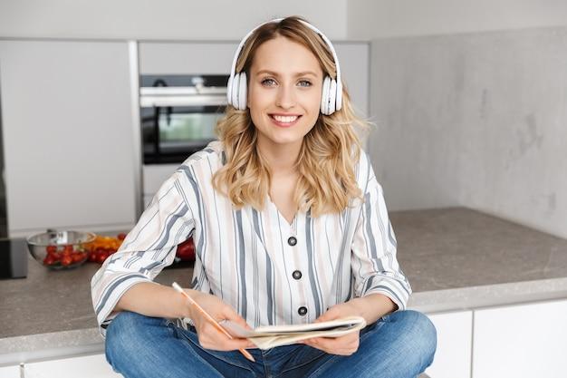 Mulher jovem e bonita ouvindo música com fones de ouvido, sentada na cozinha, fazendo anotações